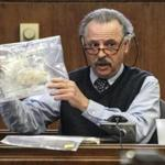 Charles Salemi, the lab supervisor of a drug analysis lab, held an evidence bag while testifying Friday during the trial for a quadruple murder in Mattapan held at Suffolk Superior Court in Boston.
